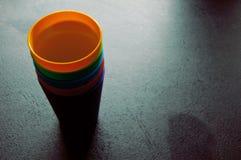 Ensemble de tasses colorées sur la table noire Images libres de droits