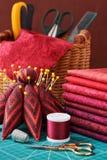 Ensemble de tissu rouge et d'outils de couture sur le tapis de métier Photo stock