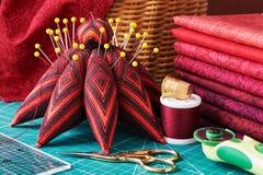 Ensemble de tissu rouge et d'outils de couture sur le tapis de métier Photos libres de droits