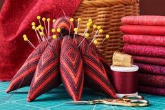 Ensemble de tissu rouge et d'outils de couture sur le tapis de métier Photos stock