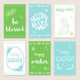 Ensemble de vecteur de cartes de voeux tirées par la main de Pâques avec le lettrage, les branches de fleur et le lapin Images libres de droits