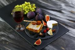 Ensemble de vin et de casse-croûte miel, verre de vin rouge, figues, raisins, écrous, variété de fromage, apéritifs et baies sur  photographie stock