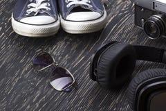 Ensemble des accessoires des hommes : espadrilles, lunettes de soleil, écouteurs et appareil-photo Photographie stock libre de droits