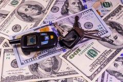 Ensemble des clés de voiture sur cent billets d'un dollar Images stock