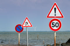 Ensemble des panneaux routiers à côté de la mer Photographie stock