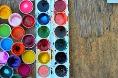 Ensemble des peintures de gouache et de l'aquarelle pour dessiner, outils artistiques sur le vieux fond en bois Image libre de droits