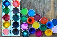 Ensemble des peintures de gouache et de l'aquarelle pour dessiner, outils artistiques sur le vieux fond en bois Photographie stock