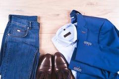 Ensemble des vêtements des hommes classiques - costume bleu, chemises, chaussures brunes, ceinture et lien sur le fond en bois Image libre de droits