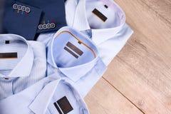 Ensemble des vêtements des hommes classiques - costume bleu, chemises, chaussures brunes, ceinture et lien sur le fond en bois Photographie stock