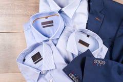 Ensemble des vêtements des hommes classiques - costume bleu, chemises, chaussures brunes, ceinture et lien sur le fond en bois Image stock