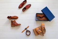 Ensemble plat de configuration de chaussures brunes non-ouvertes et de quelques accessoires bruns Photo libre de droits