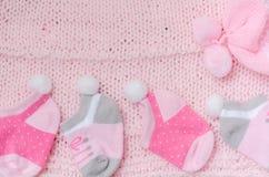 Ensemble rose de chapeau de knit et de cadeau de chaussettes pour un bébé nouveau-né sur le knit Photographie stock libre de droits