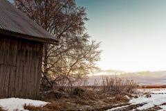 Ensembles de Sun d'hiver derrière une vieille Chambre de grange Image stock