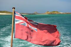 Ensign. British naval ensign with small islands behind stock photo