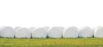 A ensilagem empilhada envolvida empacota a fileira, isolada em volta do plástico branco Fotos de Stock