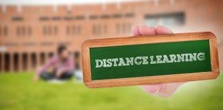 Ensino à distância contra os estudantes que usam o portátil no gramado contra a construção da faculdade foto de stock