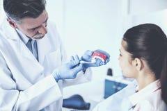 Ensino alegre do dentista no modelo dos dentes humanos como direito para escovar os dentes seu paciente fêmea fotos de stock royalty free