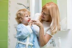Ensino da mãe e filho de ajuda da criança como escovar seus dentes fotos de stock royalty free