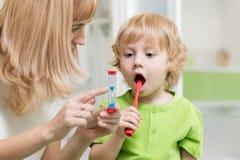 Ensino da mãe e filho de ajuda da criança como escovar seus dentes fotografia de stock