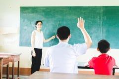 Ensino do professor na sala de aula com fundo do quadro fotografia de stock
