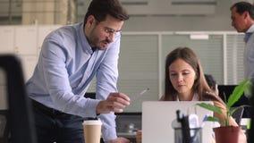 Ensino masculino do interno do treinamento do gerente do mentor que ajuda com trabalho do computador filme