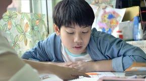 Ensinos da mãe e da criança e fazer seus trabalhos de casa imagens de stock