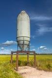 Enslig silo i ett grönt fält Arkivfoto