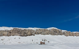 Ensligt hus under Snö-korkad bergskedja Royaltyfri Foto