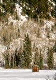 Ensligt uthus i vinter på grunden av ett berg Arkivfoton