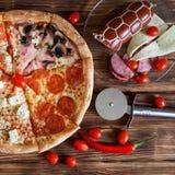 Enstycke pizza med peperoni-, skinka-, champinjon-, salami-, ost- och tomatlögner på träbräden bredvid produkterna och aet arkivbilder