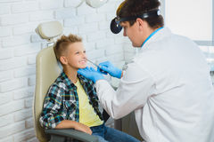Ent doctor or Otolaryngologist examining a kid nose Royalty Free Stock Images