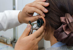 ENT physician checking patient's ear using otoscope with an inst Royalty Free Stock Image