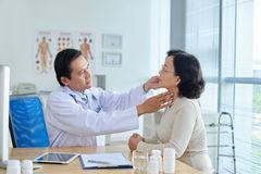 ENT Specialist Examining Patient. Concentrated middle-aged ENT specialist examining senior Asian patient while sitting at office desk, profile view royalty free stock image