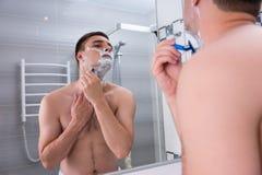 Entblößen Sie den jungen Mann, der seinen Kasten rasiert und den Spiegel betrachtet Stockfotos