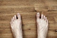Mann-Füße auf Parkett Stockbild