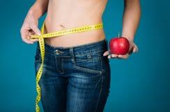 Ente femminile adatto con la mela e nastro di misurazione su fondo blu Forma fisica sana e mangiare concetto di stile di vita immagine stock