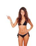 Ente femminile attraente con il bikini nero che indica qualcosa Fotografia Stock