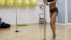 Ente sexy del ballerino femminile che ha addestramento vicino al palo nello studio luminoso di forma fisica video d archivio