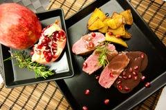 Entenbrust mit Granatapfel, Kartoffeln und Rosmarin lizenzfreies stockfoto