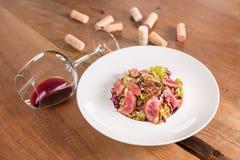 Entenbrustsalat mit Glas Rotwein stockbild