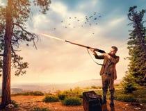Entenjäger in der Jagdkleidung zielt ein altes Gewehr stockbild