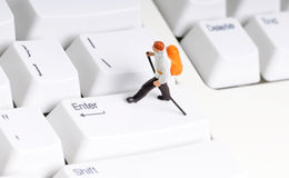 Enter. Tiny figure of hiker walking on enter key Royalty Free Stock Images
