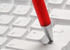 Enter. Pressing enter button on a pc keyboard with the pen Stock Photos