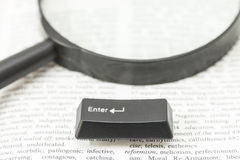 Enter Computer Key and a Lens on a Book Page Stock Image