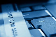 Enter key and credit card. Blue toned Royalty Free Stock Image