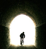 Enter the light. Unused train tunnel on a mountain biking trail, minor motion blur royalty free stock photos