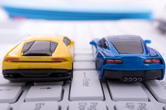 Enter Race. Two toy cars, one blue and one yellow, lined up to race at the enter key of a computer keyboard. A race to finish royalty free stock photos