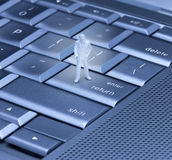 Enter Return Computer Keyboard. A small figure of a businessman standing on the enter key on a computer keyboard Stock Photography