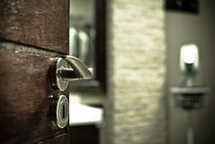 Enter the Room. Entering a room. Extreme depth of field on door handle and grungy desturated colors Stock Photo