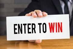 Enter to win, message on white card and hold by businessman Royalty Free Stock Photos